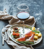 Wine appetizer set. Glass of red wine, vintage dinnerware, brushetta with cherry, dried tomatoes, arugula, parmesan, smoked meat o Stock Photography