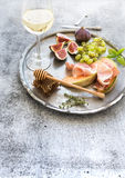 Wine appetizer set. Glass of white wine, honeycomb Royalty Free Stock Images