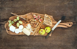 Wine appetizers set: cheese selection, honey, grapes, almonds, walnuts, bread sticks, figs on olive wood serving board royalty free stock photos
