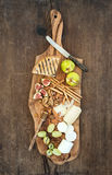 Wine appetizers set: cheese selection, honey, grapes, almonds, walnuts, bread sticks, figs on olive wood serving board Royalty Free Stock Photography