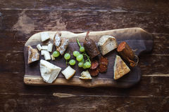 Wine appetizers set: meat and cheese selection. Grapes and bread on a rustic wooden board over a dark wood background. Top view Royalty Free Stock Photo