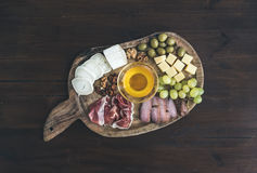 Wine appetizers set: meat and cheese selection, honey, grapes, w Royalty Free Stock Photo