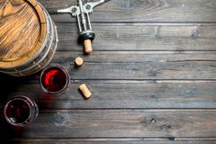 Wine background. A barrel of red wine with a corkscrew. On a wooden background royalty free stock image