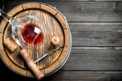 Wine background. A barrel of red wine and a corkscrew. On a wooden background royalty free stock photos