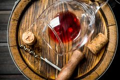 Wine background. A barrel of red wine and a corkscrew. On a wooden background royalty free stock images