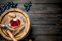 Wine background. Barrel with red wine and grapes. On a wooden background royalty free stock photo