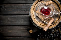 Wine background. Barrel with red wine and grapes. On a wooden background stock images