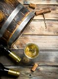 Wine background. Barrel of white wine. On a wooden background royalty free stock image