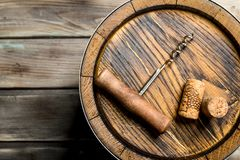 Wine background. Barrel of wine and a corkscrew from the top. On a wooden background stock image