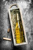 Wine background. A bottle of white wine in an old box. Royalty Free Stock Photo