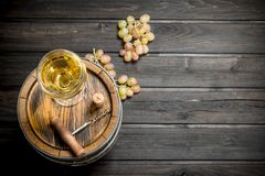 Wine background. An old barrel of white wine. On a wooden background royalty free stock photo