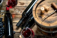 Wine background. Red wine with fresh grapes and an old barrel. On a wooden background stock photos