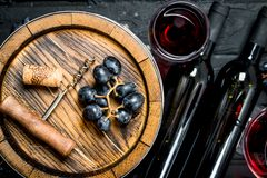 Wine background. Red wine with grapes and an old barrel. On a black rustic background stock photos