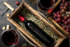 Wine background. Red wine in an old box with a corkscrew. Stock Image