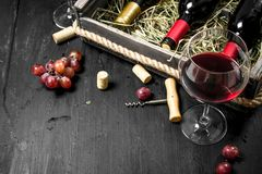 Wine background. Red wine in an old box with a corkscrew. Royalty Free Stock Photo
