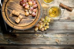 Wine background. White wine in an old barrel. On a wooden background stock images