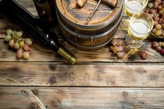 Wine background. White wine in an old barrel. On a wooden background royalty free stock photo