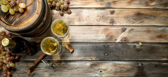 Wine background. White wine in an old barrel. On a wooden background stock photos