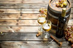 Wine background. White wine in an old barrel. On a wooden background royalty free stock photography
