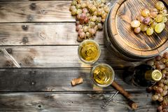 Wine background. White wine in an old barrel. On a wooden background stock photo