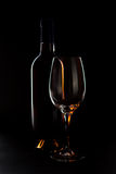 Wine in Backlight. Wine glass and bottle in backlight isolated over a black background stock photos