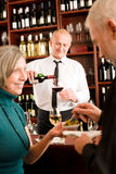 Wine bar senior couple barman pour glass Stock Photo