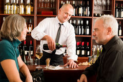 Wine bar senior couple barman pour glass. Wine bar senior couple enjoy drink professional barman pour glass stock image