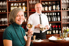 Wine bar senior woman enjoy wine glass. Wine bar senior women enjoy wine glass in front of bartender Stock Image