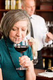 Wine bar senior woman taste wine glass stock photography