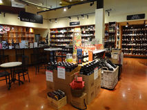 Wine Bar in a Specialty Supermarket. Tables and chairs amongst displays inside a wine bar, in the back section of a specialty supermarket, the go-to place for stock image