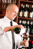 Wine bar waiter pour glass in restaurant. At the bar - waiter pour red wine in glass restaurant Royalty Free Stock Images