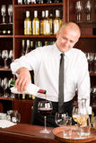 Wine bar waiter pour glass in restaurant. At the bar - waiter pour red wine in glass restaurant Stock Photography