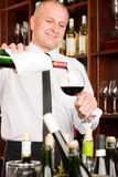 Wine bar waiter pour glass in restaurant. At the bar - waiter pour red wine in glass restaurant Royalty Free Stock Image