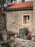 Wine barrel in front of an old house in Valun. Island Cres, Croatia Royalty Free Stock Image