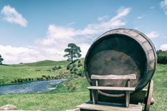 Wine Barrel in Green Grass Field in Vintage Tone. Vintage-style image of wine barrel on cart against green grass field in countryside agriculture landscape stock photos