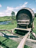 Wine Barrel in Green Grass Field in Vintage Tone. Vintage-style image of wine barrel on cart against green grass field in countryside agriculture landscape stock images