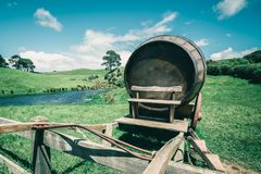 Wine Barrel in Green Grass Field in Vintage Tone. Vintage-style image of wine barrel on cart against green grass field in countryside agriculture landscape royalty free stock image