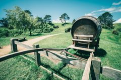 Wine Barrel in Green Grass Field in Vintage Tone. Vintage-style image of wine barrel on cart against green grass field in countryside agriculture landscape royalty free stock photo