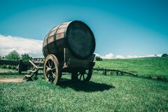 Wine Barrel in Green Grass Field in Vintage Tone. Vintage-style image of wine barrel on cart against green grass field in countryside agriculture landscape royalty free stock photos