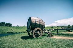 Wine Barrel in Green Grass Field in Vintage Tone. Vintage-style image of wine barrel on cart against green grass field in countryside agriculture landscape stock image