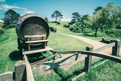 Wine Barrel in Green Grass Field in Vintage Tone. Vintage-style image of wine barrel on cart against green grass field in countryside agriculture landscape stock photography