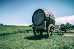 Wine Barrel in Green Grass Field in Vintage Tone. Vintage-style image of wine barrel on cart against green grass field in countryside agriculture landscape royalty free stock photography