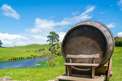 Wine Barrel in Green Grass Field. Wine barrel on cart against green grass field in countryside agriculture landscape background. Organic food, winery and alcohol stock image