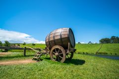 Wine Barrel in Green Grass Field. Wine barrel on cart against green grass field in countryside agriculture landscape background. Organic food, winery and alcohol royalty free stock image
