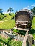 Wine Barrel in Green Grass Field. Wine barrel on cart against green grass field in countryside agriculture landscape background. Organic food, winery and alcohol stock photos
