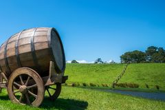 Wine Barrel in Green Grass Field. Wine barrel on cart against green grass field in countryside agriculture landscape background. Organic food, winery and alcohol royalty free stock photos