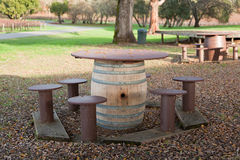 Wine Barrel Picnic Table. A picnic table made from a used wine barrel a wooden top and wooden stools sits outside at a California vineyard Stock Photo