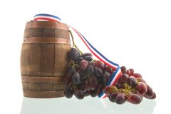 Wine barrel and red grapes. Old wooden wine barrel and buch of red grapes isolated over white background royalty free stock photo