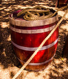Wine barrel with rope. Wine, wooden barrel with red rope on the background of natural landscape, stands on burnt grass royalty free stock photography