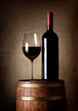 Wine on a barrel. Wine standing on a barrel on a background of a canvas royalty free stock photos